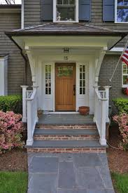 main entrance tile design below wooden front porch posts on white color also