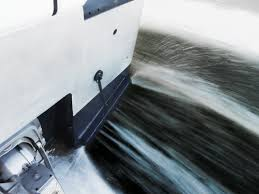 water deflects off a zipwake interceptor when it s lowered into the water to level the boat s