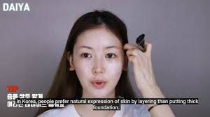 she started by putting a makeup base noting that koreans opt for a natural look and avoid thick foundation she used a pinkish base on the anese side