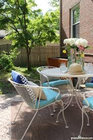 a tan metal patio set with aqua cushions pillows and a flower centerpiece