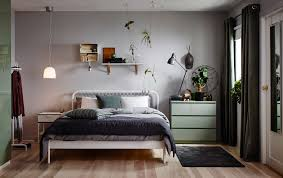 A small bedroom furnished with a bed for two in white metal with square  patterned metal