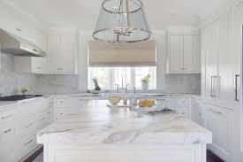 white u shaped kitchen with marble slab backsplash