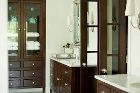 dark brown freestanding linen cabinet with glass doors