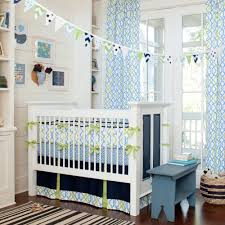 trendy blue themed nursery idea with baby boy crib bedding decorated with patterned banners and curtain