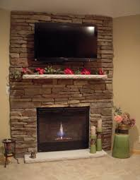 corner stacked stone gas fireplace with tv above