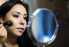 a woman looking in a small mirror putting blush on her face