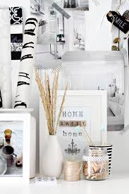 close up of the decorations on the desk which include rolls of black and white paper black white home office inspiration