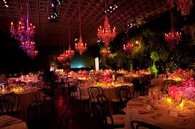 pink and purple crystal chandeliers hung above the gala dinner s round tables