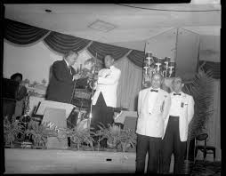 Jack Petrill, holding microphone, standing next Atty. Henry R. Smith, with  Harry Washington and Byron Peters Sr. in foreground, standing in Gateway  Plaza ballroom for FROGS formal, another version   CMOA Collection