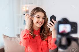 stock photo woman recording eye makeup tutorial video at home