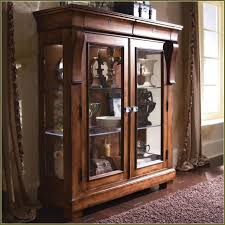 brown wooden display cabinet with glass door combined with brown carpet on brown laminated