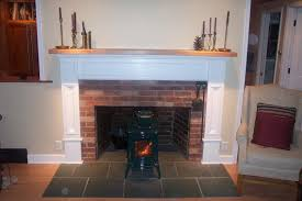 interior white fireplace mantel with brown wooden top with red brick stone fireplace connected by