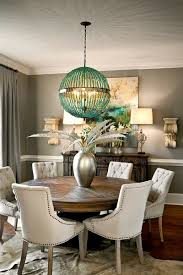 classic gray dining area with round wood dining table and white tufted dining chair under round pendant light