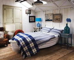 unique beach inspired bedroom design with custom wooden boat for bed frame painted with white color combined with blue bed cover and hardwood floor tiles beach inspired bedroom furniture