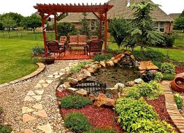 diy paver and gravel walkway to backyard pergola next to small pond with fountain