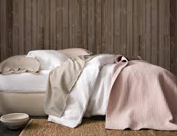 a neutral bed made with eileen fisher washed linen bedding in pure white and pebble and