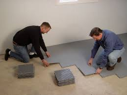 two contractors installing thermaldry floor matting tiles on a basement floor