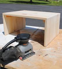 use a sander to smooth out the wood on this diy laptop table