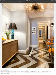 Eclectic foyer with sea urchin pendant chandelier, coffee stained wood  floors with painted silver chevron herringbone pattern, orange Louis  chairs, ...