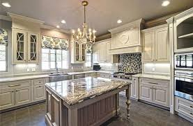traditional luxury kitchen with antique white cabinets chandelier granite island and mosaic backsplash