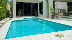outdoor in ground backyard swimming pool with glass panel fencing
