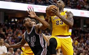 cavaliers lebron james drives to the basket against the spurs kawhi leonard in the