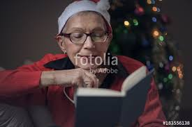 senior old lady reading her favorite book during december holiday house decorated with a