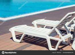 swimming pool wooden deck hotel summer sunny day lounge chairs stock photo