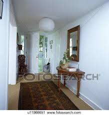 oriental rug on carpet. Brown Oriental Rug On Sisal Carpet In White Country Hall With Paper Globe Lampshade And Mirror Above Console Table