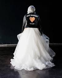 bride in wedding dress wearing leather jacket that says just married with a heart