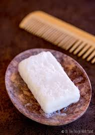 overhead view of a homemade shampoo bar in a stone soap dish next to a