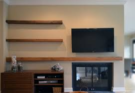 wall mounted tv and barn wood floating shelves over fireplace also a console cabinet idea