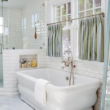 in white beveled subway tiles framing windows dressed n blue and green stripe cafe curtains over a freestanding tub and a wall mount vintage style tub