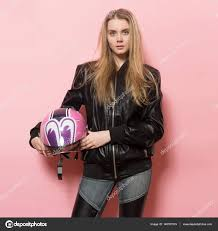 biker girl wearing black leather jacket holding pink motorcycle helmet photo by janifest