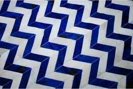 top view of a chevron blue and white cowhide patchwork rug
