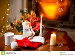 Lighting Socks On Fire Candles Woolen Socks And Santa Hat Lying On Table Against