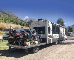freedom hauler pictured behind motorhome with quadotorcycles on board