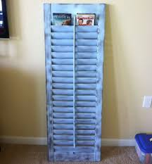 this old shutter was painted and repurposed to be a dvd holder