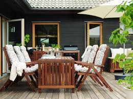 outdoor furniture small balcony. deck with six wooden reclining chairs cushions around a table black barbeque behind outdoor furniture small balcony o