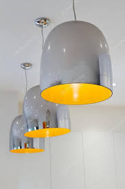 three chrome and yellow contemporary kitchen pendant lighting stock photo