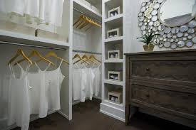 master bedroom walk in closet features stacked clothes rails next to a vertical built in shelf lined with shoes and a freestanding chest bachelors accent