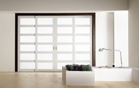 modern l shape white indoor plant container including sliding white glass interior door and large white wood framed frosted glass room divider image