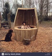 father and son in a outdoor hot tub being watched by labradoodle dog b11