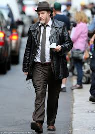 getting in character donal donned a leather coat over a brown suit with a white