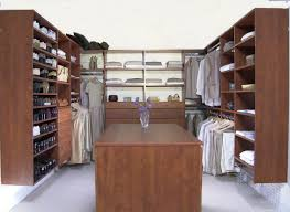 large walk in closet with center island and wire laundry basket in a cherry finish