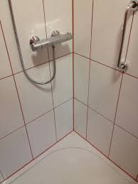 white tiles with red silicone and grout with bathroom installation in leeds