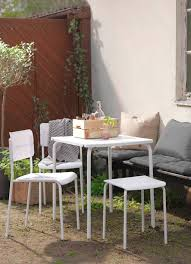 A Sunny Backyard With A White Table, Two Chairs And Stool.