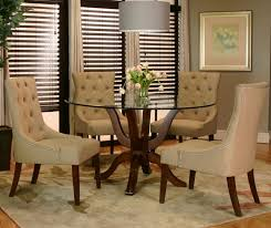 dining room curving brown wooden legs with round glass top combined with cream leather chairs