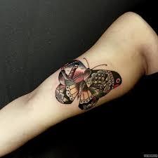 бабочка с маяком в узоре тату на бицепсе у девушки добавлено