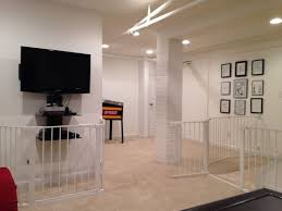 a finished basement with the entertainment center gated off an additional gate to limit access to the staircase the laundry room